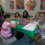 Girls sitting around table working on coloring books