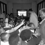 The students of Holy Angels School thank Mayor Harold Washington with a green lei for attending their 1987 St. Patrick's Day rally. Source: Harold Washington Archives and Collections: Press Office Photographs, Box 60, Folder 5. Photographer: Antonio Dickey